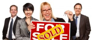 Woman Holding Keys and Sold Sign